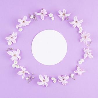Papier blanc rond dans un cadre de fleurs