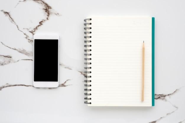 Papier blanc, smartphone et crayon sur fond de marbre blanc