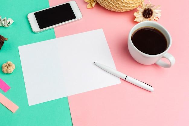 Papier blanc avec un téléphone intelligent sur le bureau