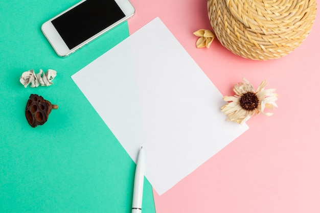 Papier blanc avec un téléphone intelligent sur le bureau.
