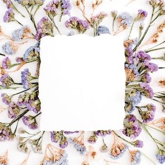 Papier blanc vide vierge sur cadre de fleurs séchées bleu et violet sur fond blanc. mise à plat, vue de dessus