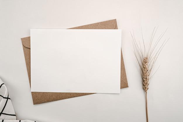 Papier blanc vierge sur enveloppe de papier brun avec fleur d'orge sèche et tissu blanc avec grille noire