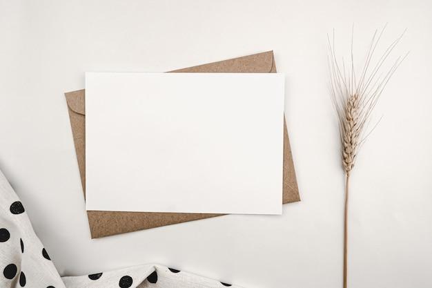 Papier blanc vierge sur enveloppe de papier brun avec fleur d'orge sèche et tissu blanc à pois noirs