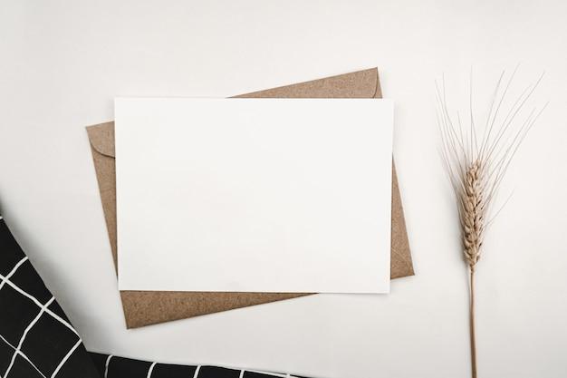Papier blanc vierge sur enveloppe de papier brun avec fleur d'orge sèche et tissu noir avec grille blanche