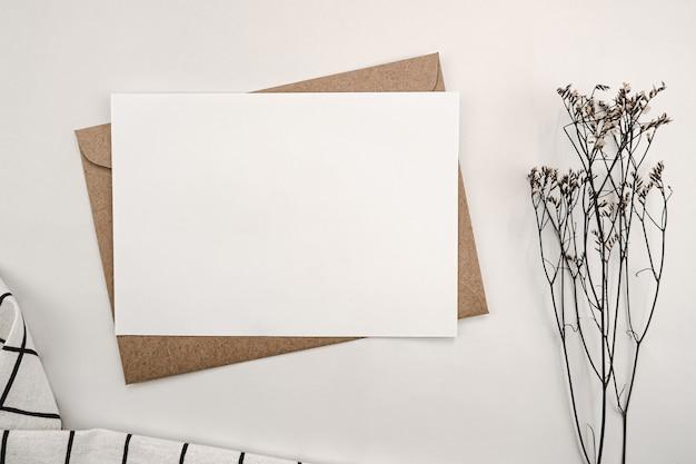 Papier blanc vierge sur enveloppe en papier brun avec fleur sèche limonium et chiffon blanc avec grille noire
