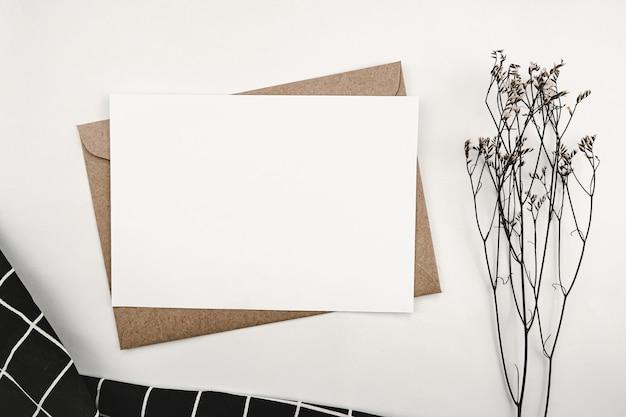 Papier blanc vierge sur enveloppe en papier brun avec fleur sèche limonium et grille blanche en tissu noir