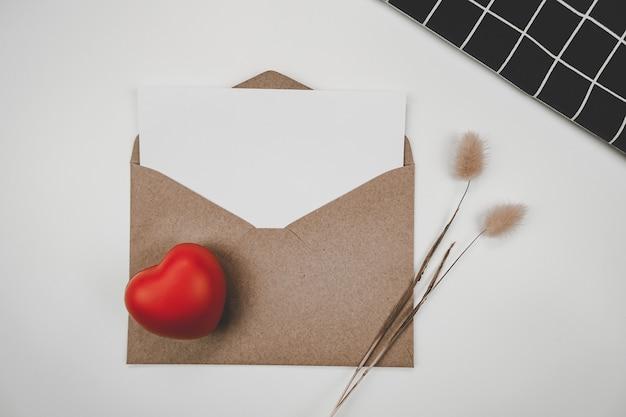 Le papier blanc vierge est placé sur une enveloppe de papier brun ouvert avec un cœur rouge, une fleur sèche de queue de lapin et un chiffon noir
