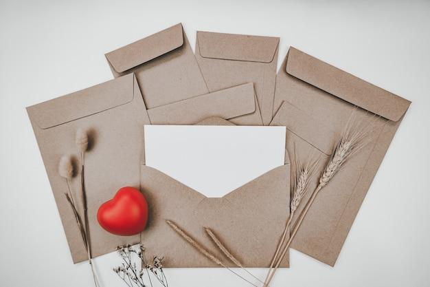 Le papier blanc vierge est placé sur une enveloppe de papier brun ouvert avec un cœur rouge, de nombreux types de fleurs séchées