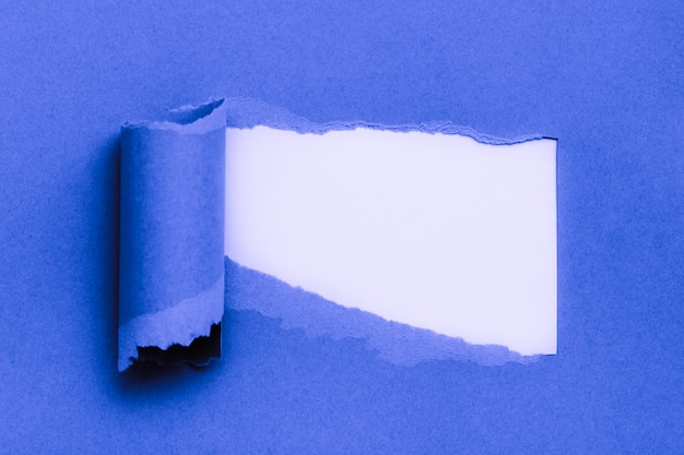 Papier bleu déchiré avec un espace pour le texte avec du blanc