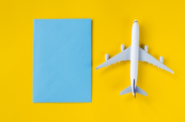 Papier bleu vide sur fond jaune avec avion décoratif. concept de voyage d'été.