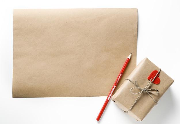 Papier de bricolage, crayon et cadeau avec coeur rouge