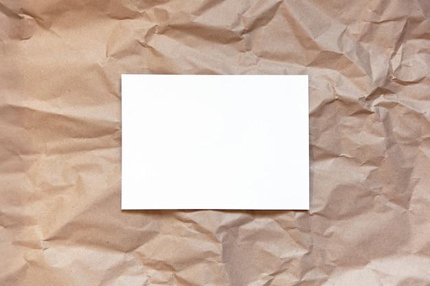 Papier brun artisanal froissé avec une feuille blanche au milieu