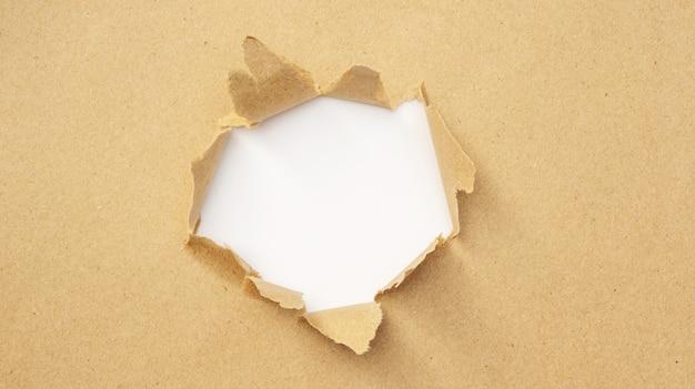 Le papier brun a été déchiré au centre.