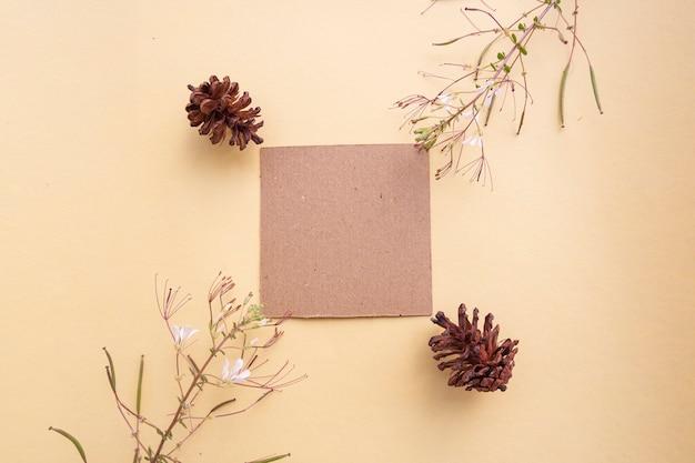Papier brun sur fond jaune pastel décoré de fleurs et de sapins. carte de visite. carte de visite, livre blanc. maquettes en papier. fond de couleur pastel
