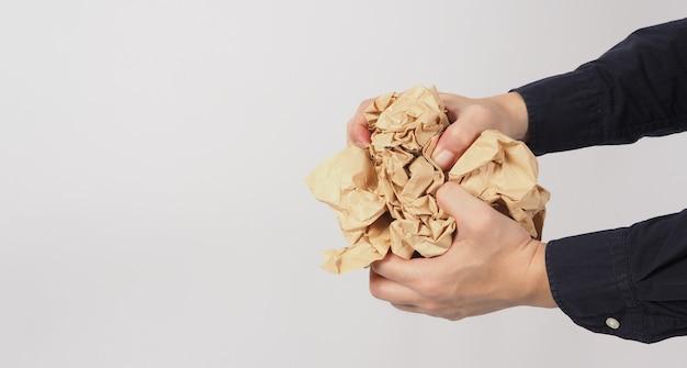 Papier brun froissé. il est mutilé dans la main de l'homme sur fond blanc.