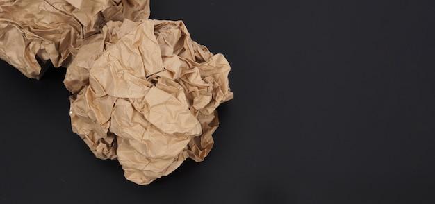 Papier brun froissé. il est mutilé sur fond noir.