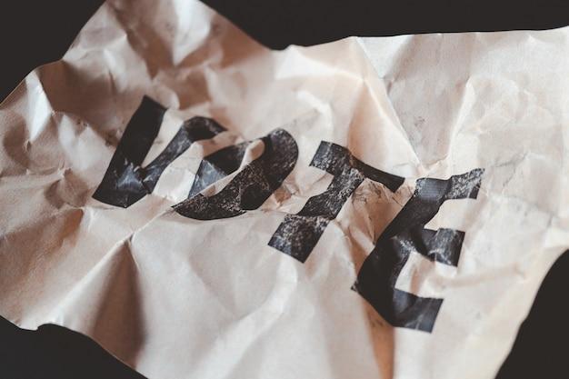 Papier brun froissé avec vote de mot imprimé,