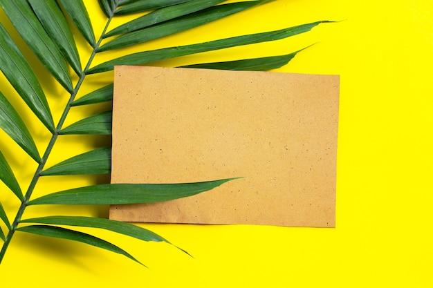 Papier brun vierge sur les feuilles de palmiers tropicaux sur jaune
