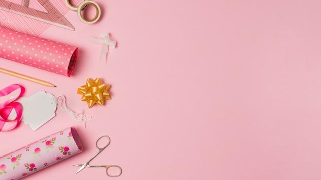 Papier cadeau; ciseaux; étiquettes et articles de papeterie sur du papier peint rose avec un espace pour le texte
