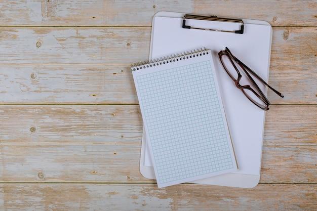 Papier de cahier vide pour le texte avec des lunettes sur fond en bois.