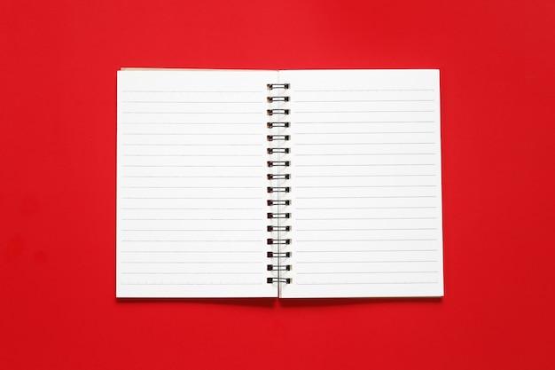Papier de cahier vierge sur un fond de papier d'art rouge.