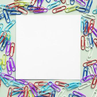 Papier carton blanc en forme de carré entouré de nombreux trombones