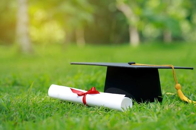 Papier de certificat en gros plan et capuchon d'éducation sur l'herbe verte au printemps dans le parc extérieur