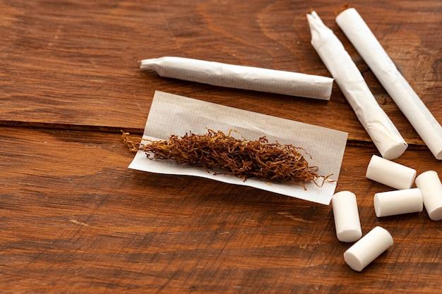 Papier à cigarettes et tas de tabac sur table en bois se bouchent