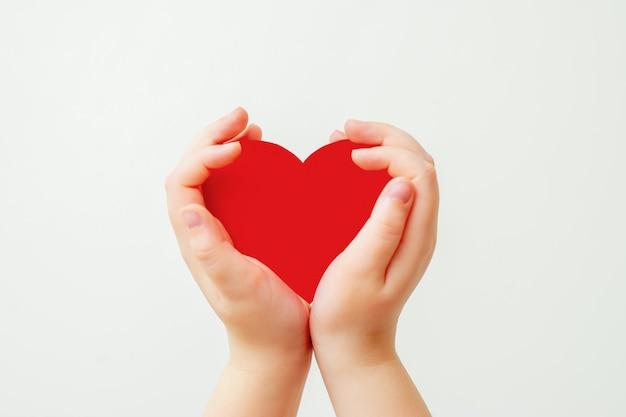 Papier coeur rouge dans les mains de l'enfant