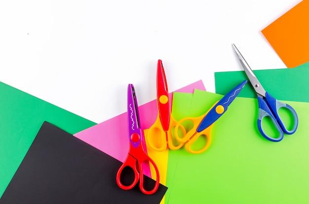 Papier coloré avec des ciseaux pour enfants sur fond blanc