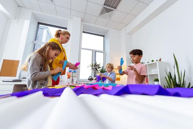 Papier coloré. enseignant et élèves utilisant du papier coloré lors de la leçon d'art à l'école primaire