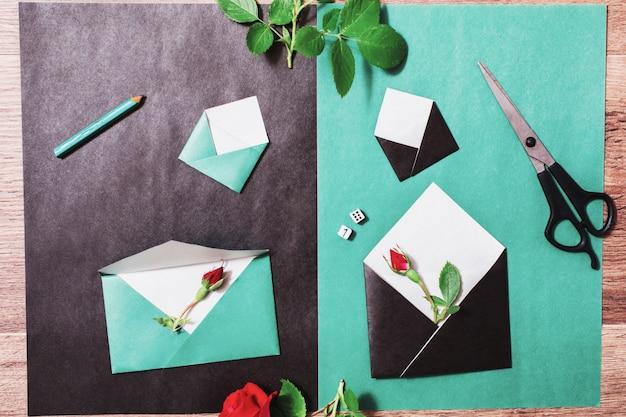Papier couleur. petites enveloppes colorées. concepteur de lieu de travail. lettre romantique. arrangement de fleurs avec des articles de papeterie. roses rouges avec des feuilles vertes sur fond en bois. mise à plat. dés pour la bonne chance