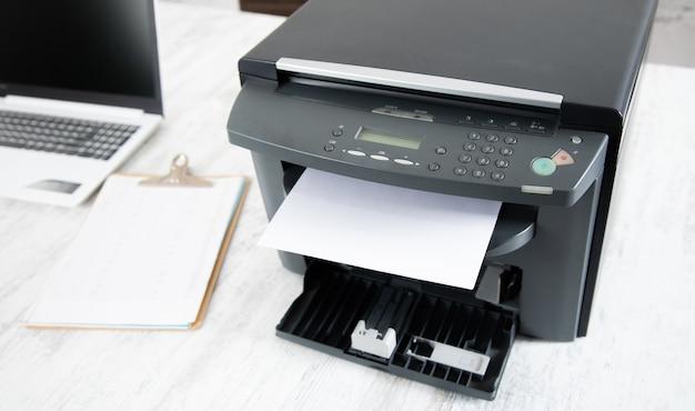 Papier dans l'imprimante et l'ordinateur sur la table