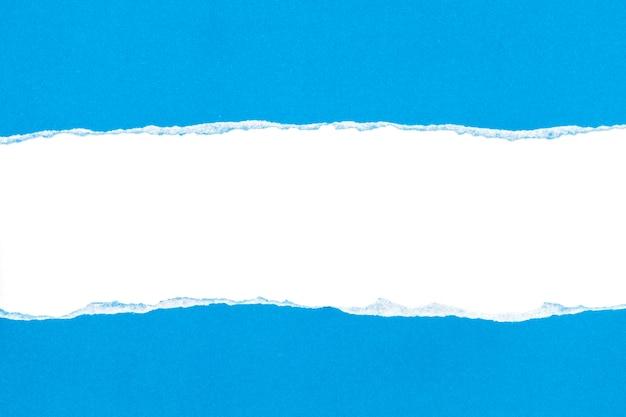 Papier déchiré bleu ouvert sur fond de papier blanc