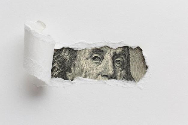 Papier déchiré révélant un billet d'un dollar