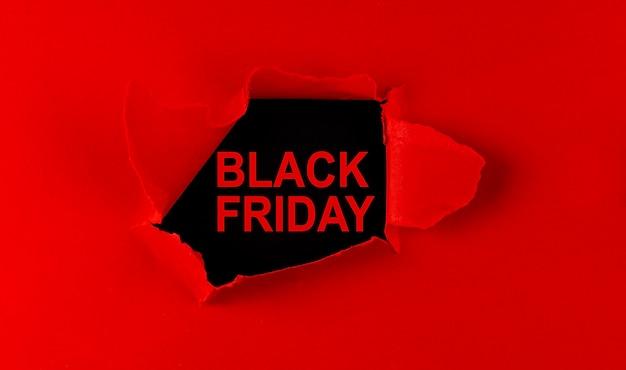 Papier déchiré rouge et inscription vendredi noir sur fond noir.
