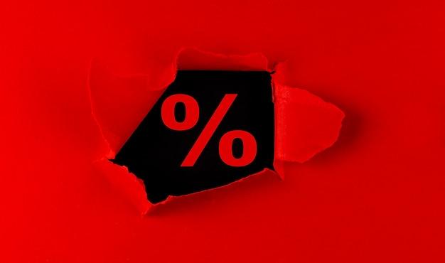 Papier déchiré rouge avec un mot pour cent sur le fond noir