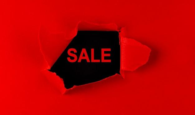 Papier déchiré rouge avec un mot vente sur fond noir