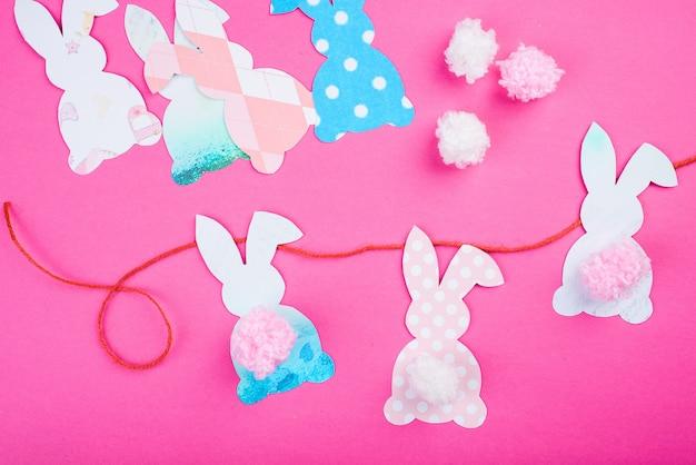 Papier de décoration de lapin de pâques coupé en arrière-plan. guirlande artisanale de vacances de bricolage de lapins colorés et d'outils d'artisanat.