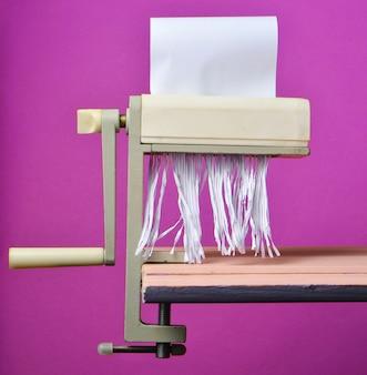 Papier découpé par une machine manuelle pour couper les pâtes sur un fond pastel rose, tendance minimaliste, style rétro
