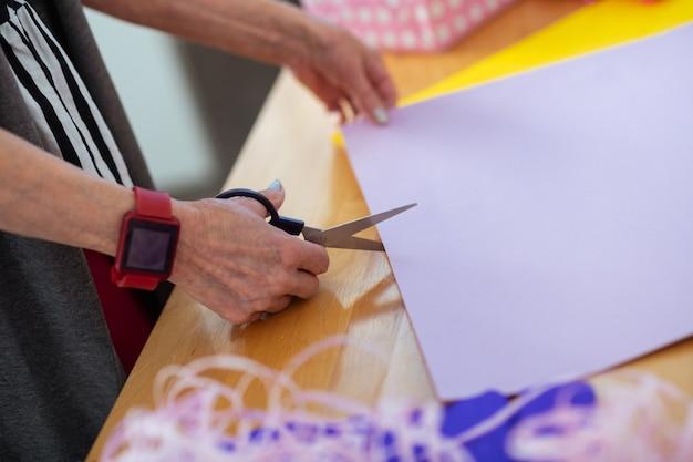 Papier à découper. vue de dessus des mains avec des ciseaux dedans tout en coupant le papier d'emballage