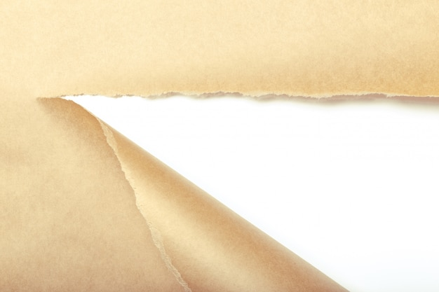 Papier d'emballage brun déchiré pour révéler le panneau blanc