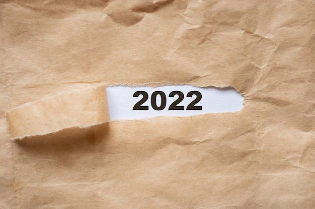 Le papier d'emballage brun est déchiré pour révéler un panneau blanc