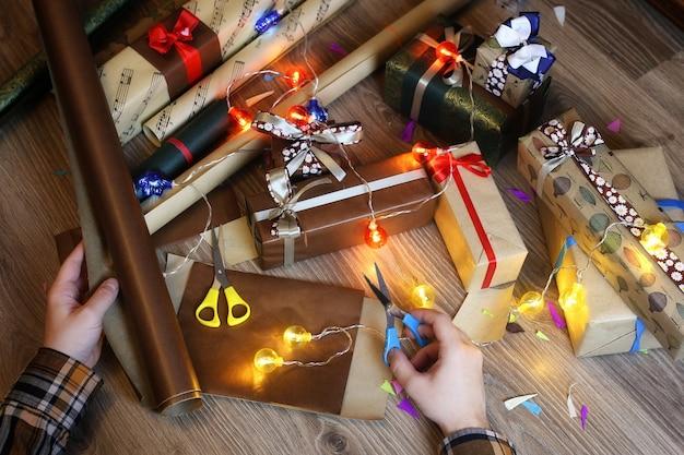 Papier d'emballage cadeau à la main pour le ruban et les arcs de noël de vacances