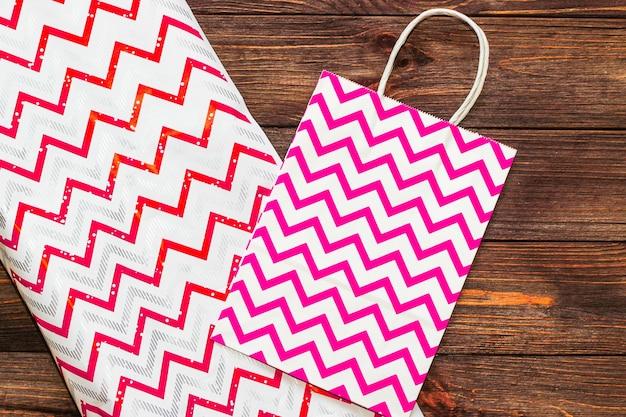 Papier d'emballage cadeau et sac rose sur fond en bois.