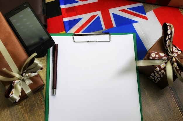 Le papier forme une texture sur une table en bois avec des coffrets cadeaux emballés avec un téléphone portable et des drapeaux