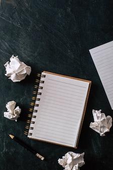 Papier froissé avec carnet de notes et un crayon sur fond noir