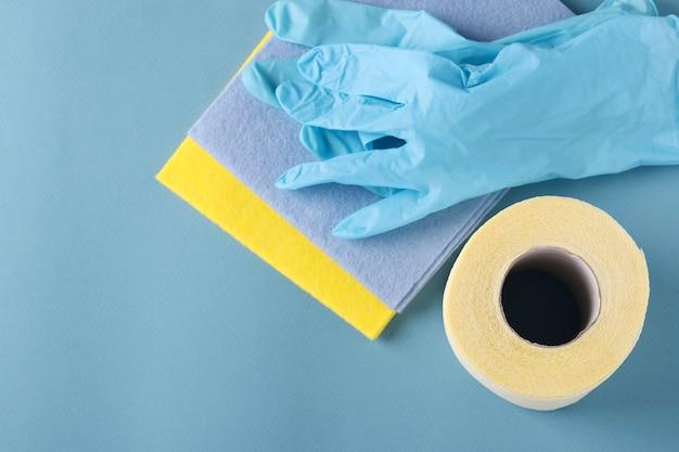 Papier hygiénique, gants et serviettes de nettoyage sur fond bleu, demande inattendue élevée, déficit, pandémie de covid-19, gros plan
