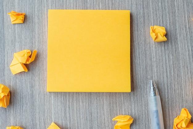 Papier jaune vide avec un stylo et du papier émietté