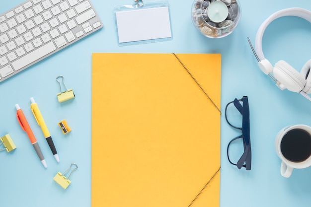 Papier jaune vierge avec bougie; clavier; casque de musique ; tasse à café et lunettes de vue sur fond bleu